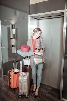 Afhaalkoffie. vrolijke vrouw die zich dichtbij lift bevindt die haar echtgenoot belt na het kopen van afhaalkoffie