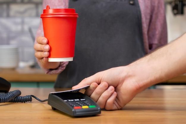 Afhaalkoffiebarista houdt een rood papieren glas vast