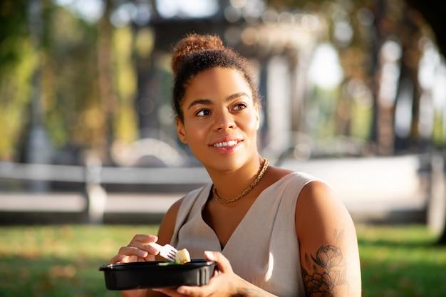 Afhaallunch eten. donkerharige aantrekkelijke vrouw die meeneemlunch eet terwijl het zitten in het park