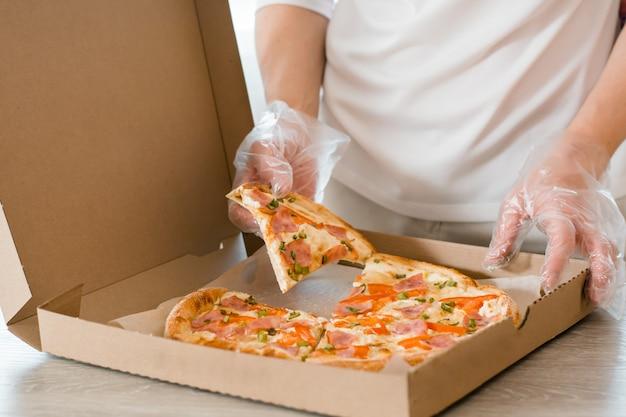 Afhaalmaaltijden. een vrouw in wegwerphandschoenen pakt een stuk pizza uit een kartonnen doos op de tafel in de keuken.
