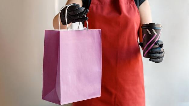 Afhaalmaaltijden paarse papieren zak mock-up. bezorging voedselzak, koffiebekerpakket drinken om mee te nemen in afhaalrestaurant. keukenmedewerker geeft bestellingen in handschoenen. lange webbanner.