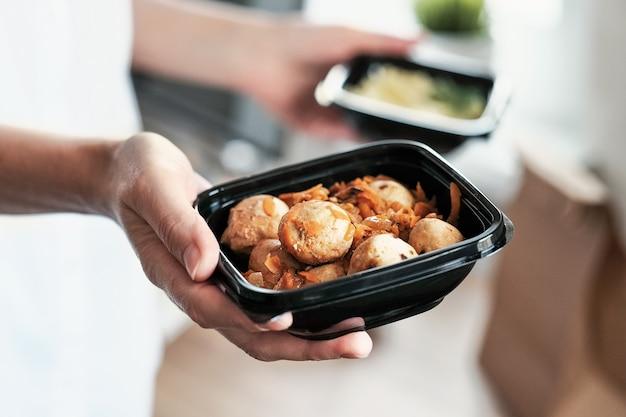 Afhaalmaaltijden. vrouwenhanden houden een kom gehaktballen vast