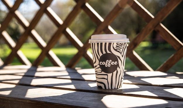 Afhaalmaaltijden wegwerpbeker met koffie op houten bankje coffee to go sunny day nature surface