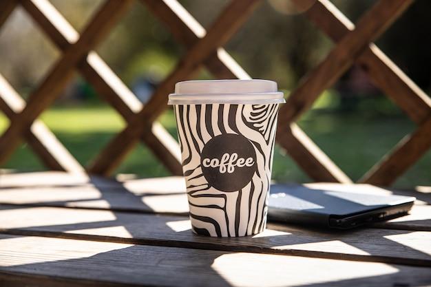 Afhaalmaaltijden wegwerpbeker met koffie op houten bankje in de ochtendtuin