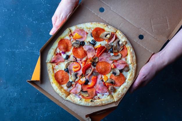 Afhaalservice. vrouwelijke hand houdt open kartonnen doos met pizza. vers bereide pizza met champignons, ham en kaas op een donkere achtergrond. fast food concept.