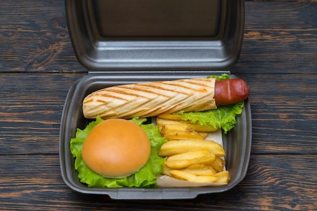 Afhaalworsthond in een gegrild stokbrood geserveerd met een hamburger en frietjes in een wegwerp polystyreen bakje