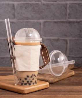 Afhalen met wegwerp item concept populaire taiwan drink bubble melkthee met plastic beker en stro op houten tafel