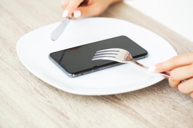Afhankelijkheid van de telefoon, close-up van de handen van een vrouw met een vork en een mes over de telefoon op plaat.