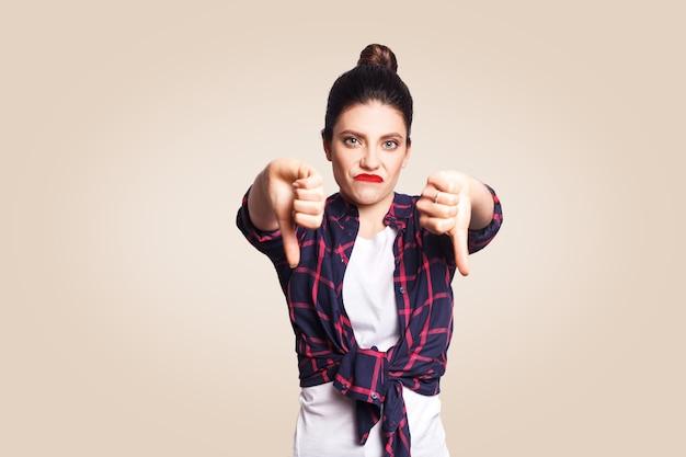 Afkeer. jong ongelukkig boos meisje met casual stijl en knot haar duimen naar beneden haar vinger, op beige lege muur met kopieerruimte camera kijken met brede glimlach. focus op gezicht.