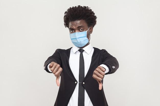 Afkeer. portret van een ontevreden jonge werknemer die een zwart pak draagt met een chirurgisch medisch masker dat zijn duimen naar beneden houdt en naar de camera kijkt. indoor studio opname geïsoleerd op een grijze achtergrond.