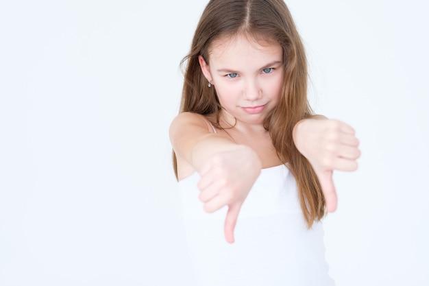 Afkeurend ontevreden kind met duim omlaag gir op witte muur.