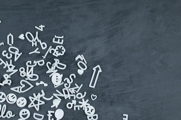 Afneembare witte letters, pictogrammen en pinnen op zwart oppervlak