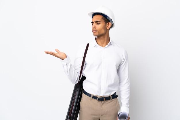 African american architect man met helm en blauwdrukken te houden over geïsoleerde witte muur bedrijf copyspace met twijfels