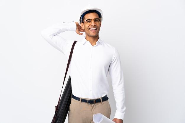 African american architect man met helm en blauwdrukken te houden over geïsoleerde witte muur _ lachen