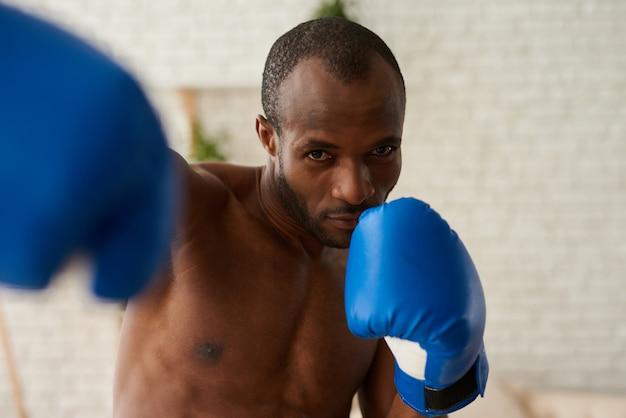 African american boksen in handschoenen thuis.