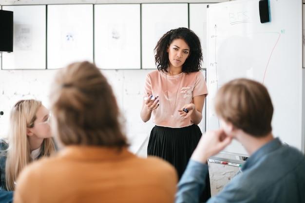 African american girl met donker krullend haar permanent in de buurt van bord en presentatie geeft aan collega's in kantoor