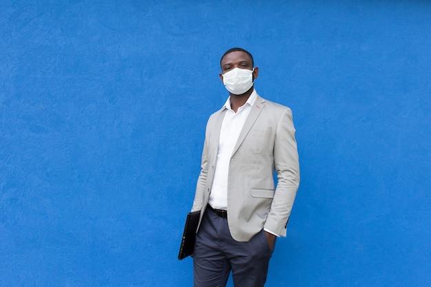 African american in een beschermend masker met een laptop in zijn hand