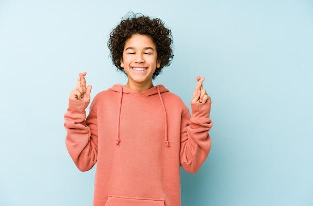 African american jongetje geïsoleerd kruising vingers voor het hebben van geluk