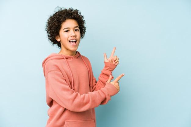 African american jongetje wijzend met wijsvingers naar een lege ruimte