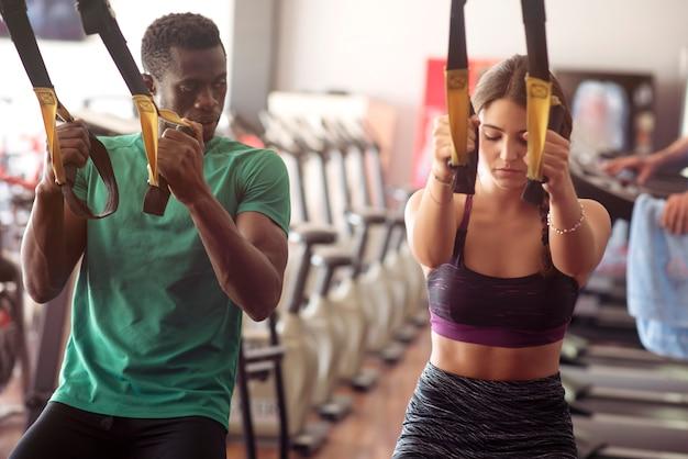African american man en jonge vrouw doen trx oefeningen