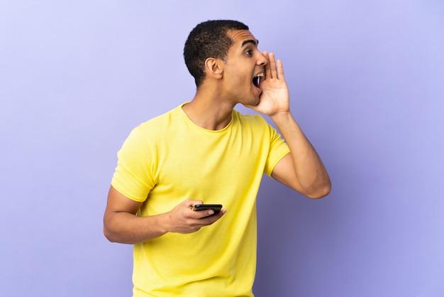 African american man over geïsoleerde paarse muur met behulp van mobiele telefoon schreeuwen met wijd open mond