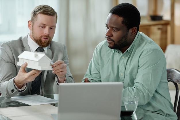 African american man zittend aan tafel met financieel adviseur en luisteren over hypotheek