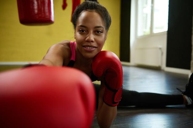 African american mooie atletische vrouw, vrouwelijke bokser in rode bokshandschoenen strekt de benen op het touw op de vloer van een sportschool en ponsen naar camera. krijgskunst en stretching