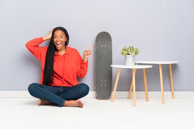African american skater tiener meisje met gevlochten haar zittend op de vloer verrast en wijzende vinger aan de zijkant