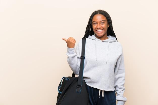 African american sport tiener meisje met lang gevlochten haar wijst naar de zijkant om een product te presenteren