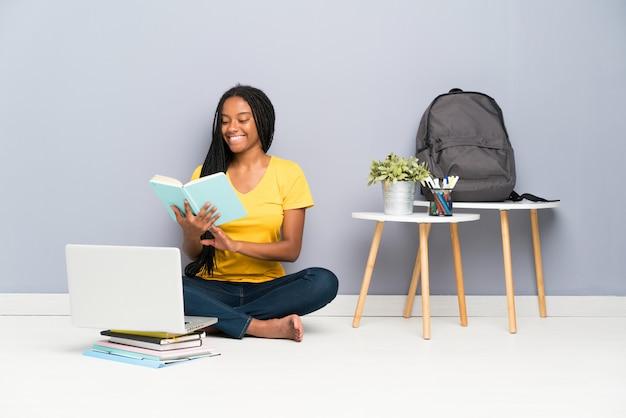 African american tiener student meisje met lang gevlochten haar zittend op de vloer en het lezen van een boek