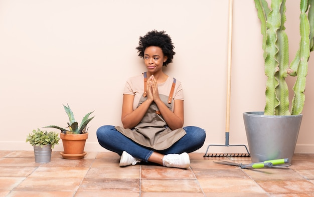 African american tuinman vrouw zittend op de vloer