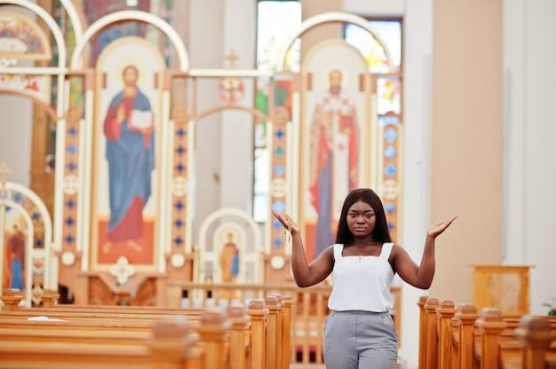African american vrouw bidden in de kerk. gelovige mediteert in de kathedraal en de spirituele tijd van gebed. afro meisje houdt handen omhoog.