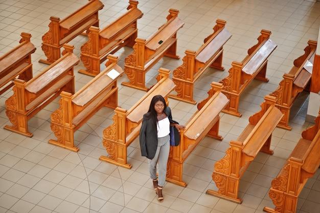 African american vrouw bidden in de kerk. gelovigen mediteren in de kathedraal en de spirituele tijd van gebed. uitzicht van boven.