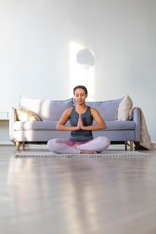 African american vrouw doet yoga thuis. gebed. lotus-positie.
