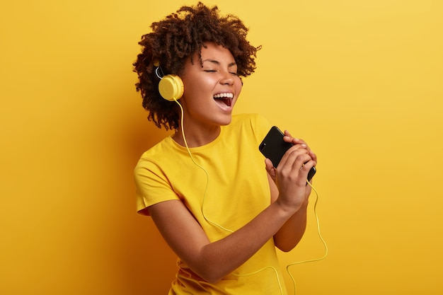 African american vrouw, gekleed in geel t-shirt en koptelefoon