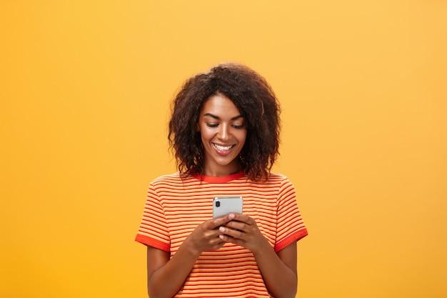 African american vrouw glimlachend vreugdevol tijdens het sms'en op een mobiele telefoon over oranje muur