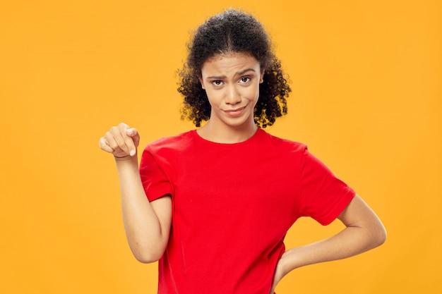 African american vrouw in een t-shirt op een gekleurde muur poseren
