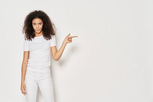 African american vrouw in een t-shirt op een muur poseren