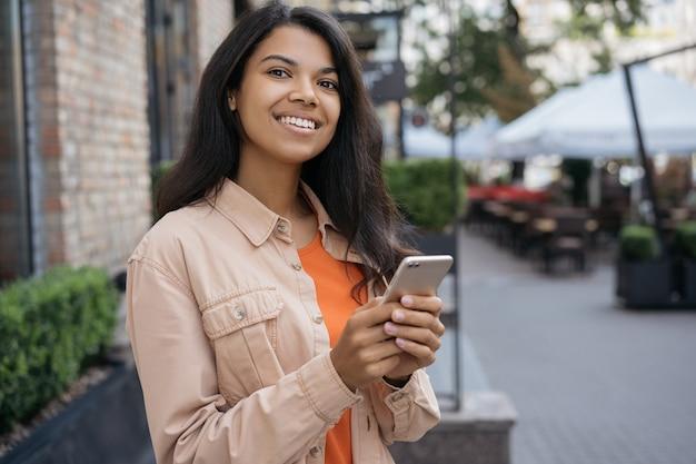 African american vrouw met behulp van mobiele telefoon, staande op straat, taxi wachten