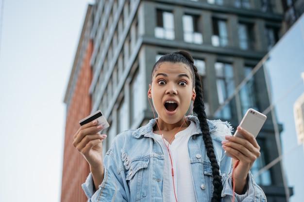 African american vrouw met creditcard bedrijf, met behulp van smartphone, online winkelen