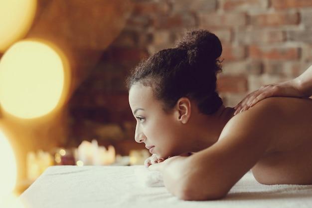African american vrouw ontvangt een ontspannende massage in de spa