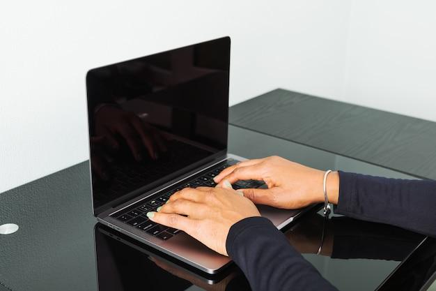 African american vrouw te typen op een toetsenbord op een moderne laptop