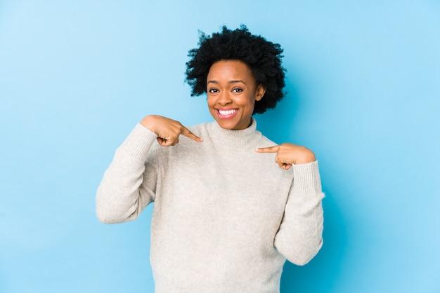 African american vrouw van middelbare leeftijd tegen een blauwe muur geïsoleerd verrast verrast wijzend met vinger, breed glimlachend.