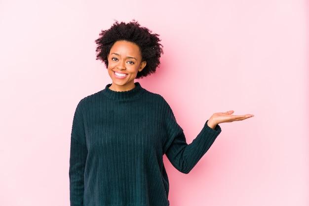 African american vrouw van middelbare leeftijd tegen een roze muur geïsoleerd met een kopie ruimte op een palm en een andere hand op de taille te houden.