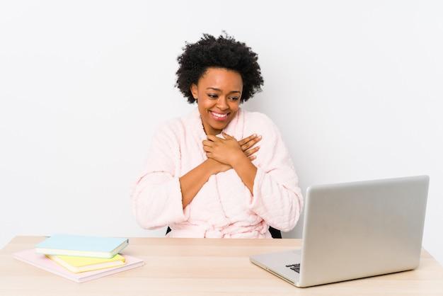 African american vrouw van middelbare leeftijd thuis werken geïsoleerd lachen hand in hand op hart, concept van geluk.