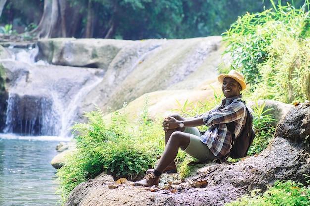 African man traveler ontspannende vrijheid bij waterval