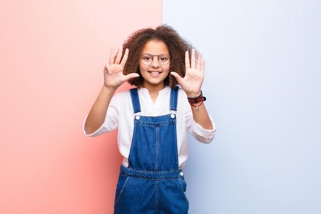 Afrikaans amerikaans en meisje die vriendschappelijk glimlachen kijken, tonend nummer negen of negende met voorwaartse hand, aftellend tegen vlakke muur