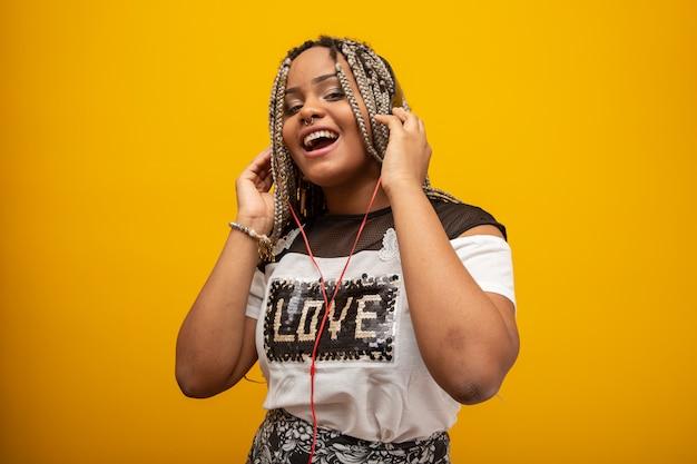 Afrikaans amerikaans meisje dat aan muziek op hoofdtelefoons op geel luistert