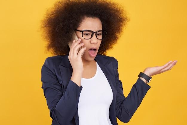 Afrikaans amerikaans meisje dat op geïsoleerde telefoon spreekt.