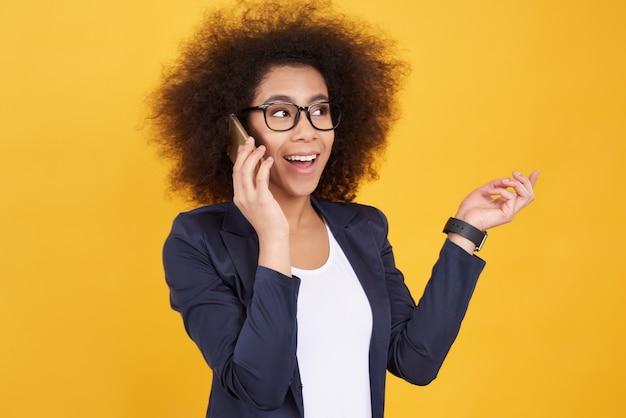 Afrikaans amerikaans meisje dat op telefoon op geel spreekt.